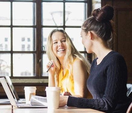 Twee vrouwen zitten op kantoor te werken achter hun laptops en lachen naar elkaar